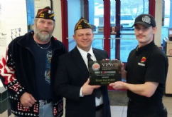 Post Commander Howard Gooldrup presents Nathan Grannan of Burger King a Plaque with the assistance of Craig DuFour (on the left).